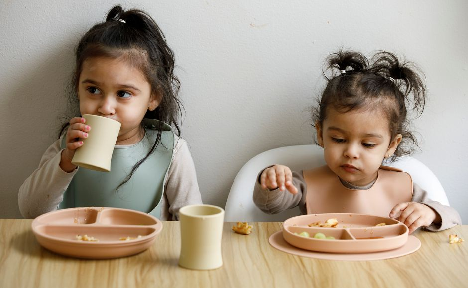 London Cominsky, 3, left, and Rowyn Velez, 1, of Meriden, enjoy waffles using silicone plates and training cups at their residence in Meriden on Wednesday.