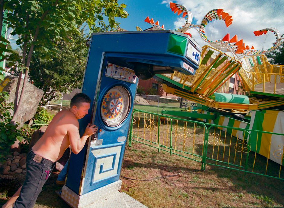 "RJ file photo - Fred Doyle of Seymour, an employee of Cheshire-based Tufano Amusements Inc. Moves the ""K.O."" boxing machine concession into place as preparations are make for the Southington Apple Harvest Festival Sept. 28, 1998."