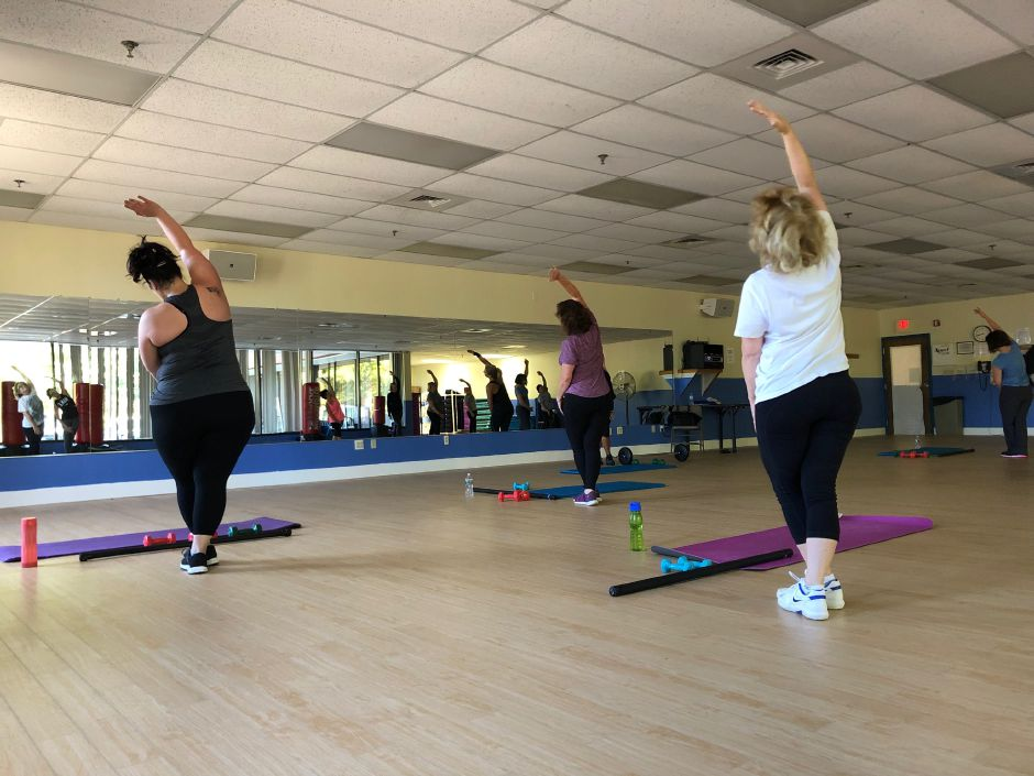 Participants stretch their backs during a Powerology class in Wallingford. |Kristen Dearborn, special to the Record-Journal