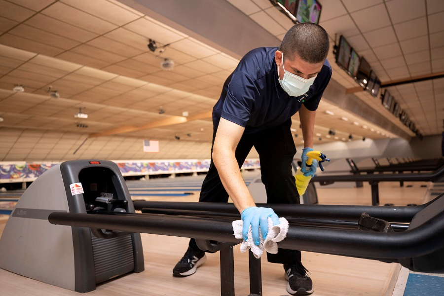 Manager Jason Scagliarini wipes down a ball return between customers at Lessard Lanes, 136 New Britain Ave., Plainville, Wednesday. Most area alleys have opened back up, and Lessard Lanes has made many adjustments to make their bowlers feel safe. Photos by Dave Zajac, Record-Journal