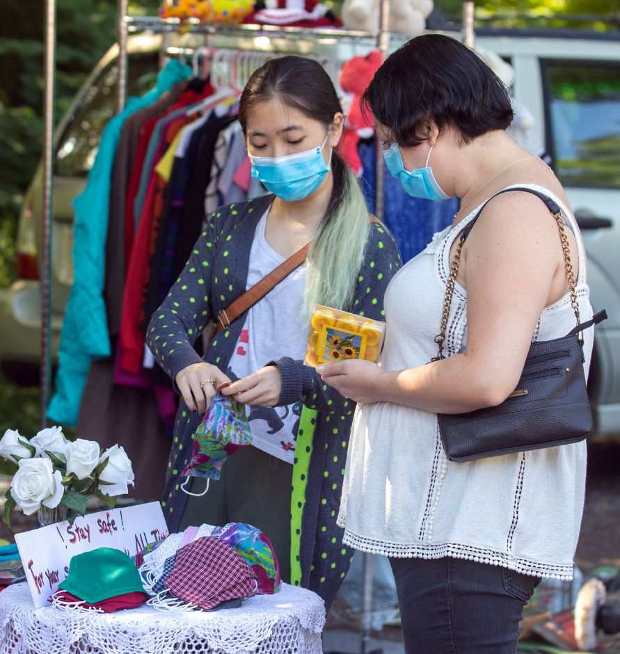 Emily Li left shows the face masks she has for sale at her booth to Krista Galante of Wilcox at the Redwood Country Fleamarket in Wallingford on Sunday, July 12, 2020. The flea market is open for business every Friday from 6 am- 2 pm and 6 am to 3 pm on Saturday and Sunday. All visitors and vendors are asked to wear a mask when at the flea market. Aaron Flaum, Record-Journal