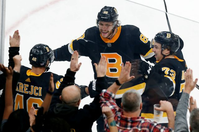 Boston Bruins' David Krejci, left,  celebrates his overtime, game-winning goal with David Pastrnak, center, and Charlie McAvoy in a 3-2 win over  the New York Rangers in Boston on  Nov. 29. Michael Dwyer, Associated Press