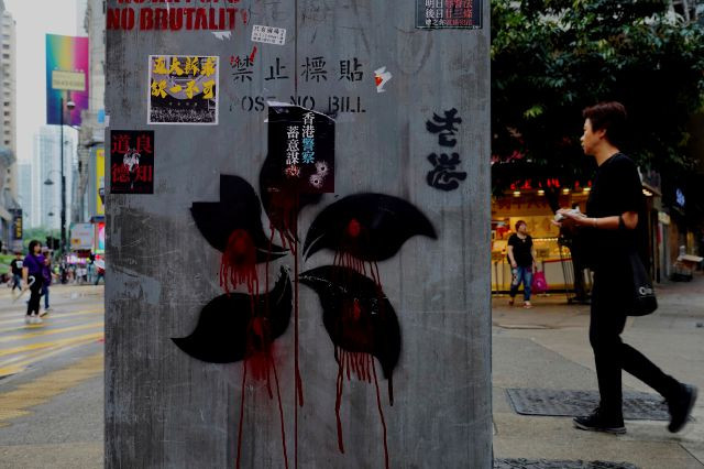 People walk near graffiti on a pillar which shows Hong Kong Special Administrative Region (SAR) flag pattern drawn in black and red in Hong Kong, Monday, Oct. 7, 2019. Tens of thousands of masked protesters marched defiantly in the city center Sunday, but the peaceful rallies quickly degenerated into chaos at several locations as hard-liners again lobbed gasoline bombs, started fires and trashed subway stations and China-linked banks and shops. (AP Photo/Vincent Yu)