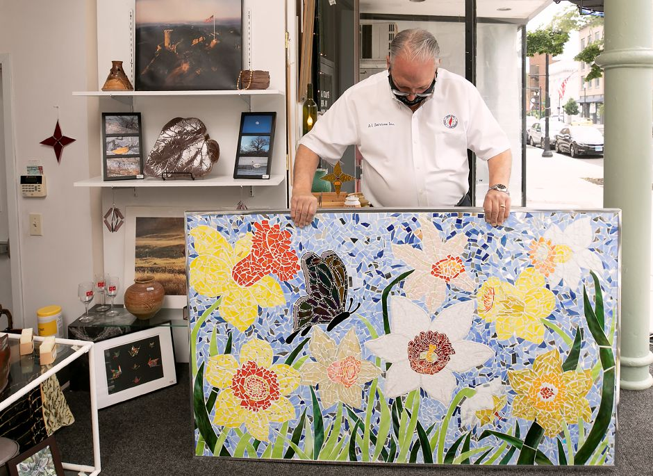 David Liseo, of Meriden, looks over a stained-glass mosaic on  Tuesday after he made the highest and winning bid for it  in Gallery 53's Animal and the Arts Auction over the weekend. The work was created by Christine Webster, Gallery 53 president, and other local artists. Liseo is the owner of A-1 Services, Inc. on Colony Street in Meriden. Photos by Dave Zajac, Record-Journal