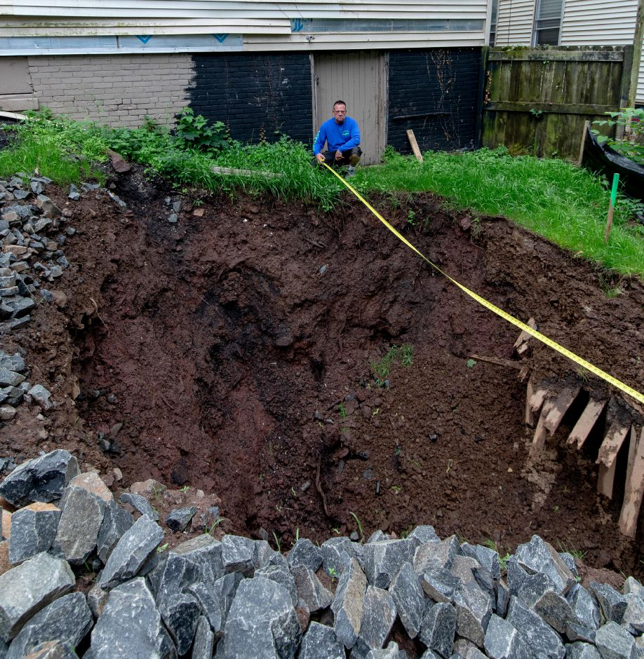 A property manager with Dockside Construction shows the size of a sinkhole which appeared in the backyard of 170 Liberty St. in Meriden on Easter morning.
