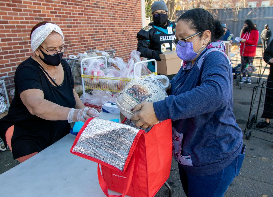 Volunteer Primy Rivera helps Belinda Martinez put a turkey into a cooler bag as Thanksgiving meals are distributed to families at the Meriden Salvation Army on Friday, November 20, 2020. Aaron Flaum, Record-Journal