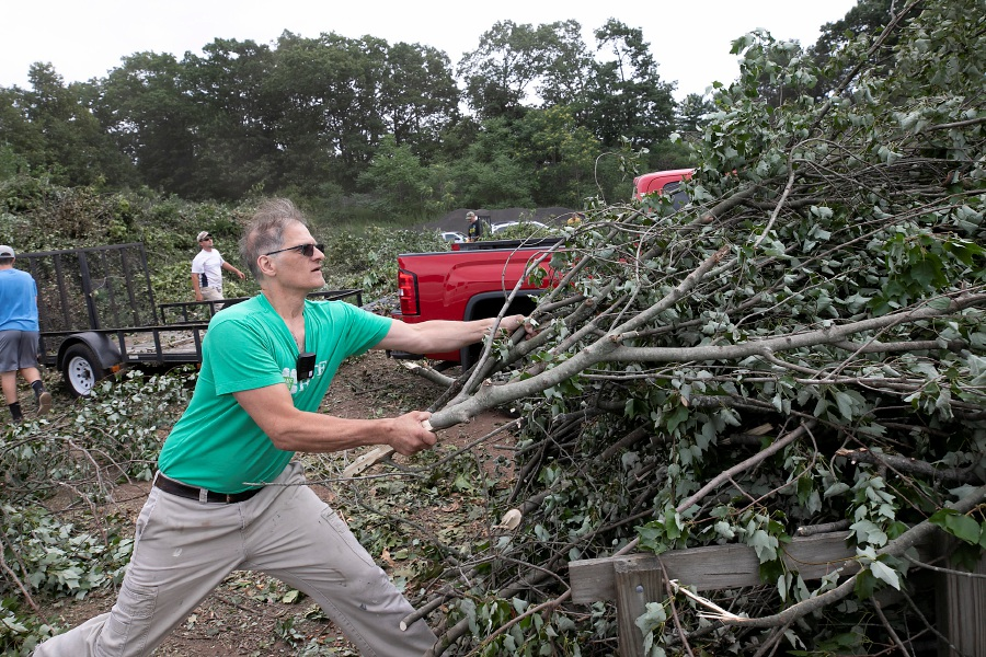 August Riedinger, of Southington, a 20-year volunteer firefighter in town, pulls a pile of brush off his trailer at the transfer station in Southington Thursday. The town's transfer station was a flurry of activity from 7:30 a.m. to 3 p.m., as residents unloaded tree limbs and other debris.