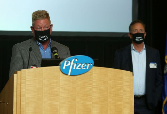 John Burkhardt, left, senior vice president of drug safety R&D and head of the Pfizer Groton site speaks at a press conference at Pfizer Groton on the companies research to develop a vaccine for COVID-19, as Connecticut Gov. Ned Lamont stands by to answer questions Wednesday, July 22, 2020, in Groton, Conn. The federal government has agreed to pay nearly $2 billion for 100 million doses of a potential COVID-19 vaccine being developed by the U.S. drugmaker and its German partner...