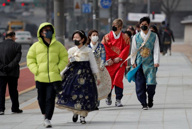REMOVES REFERENCE TO NUMBER OF VIRAL INFECTIONS - Visitors wearing face masks walk near the Gwanghwamun, the main gate of the 14th-century Gyeongbok Palace, and one of South Korea