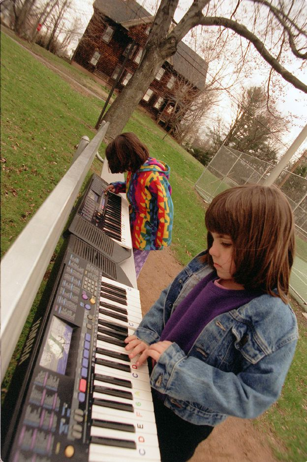 Elizabeth Spiteri, background, and Jennifer Ruocco, foreground, play electronic keyboards across the street from the Wallingford YMCA on South Main Street April 7, 2000. The two are participating in the kindergarten childcare program. Kids rotated betwween toys and keyboards in the nice weather.