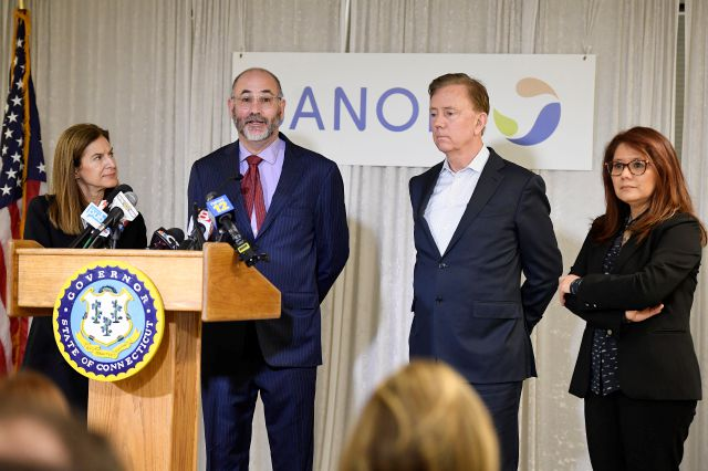 Clem Lewin, associate vice president of research and development strategy at Sanofi speaks to the media as Lt. Gov. Susan Bysiewicz, left, Connecticut Gov. Ned Lamont, second from right, and Mireli Fino, site head at Protein Sciences, listen during visit by the governor to Protein Sciences, Thursday, March 12, 2020, in Meriden. (AP Photo/Jessica Hill)