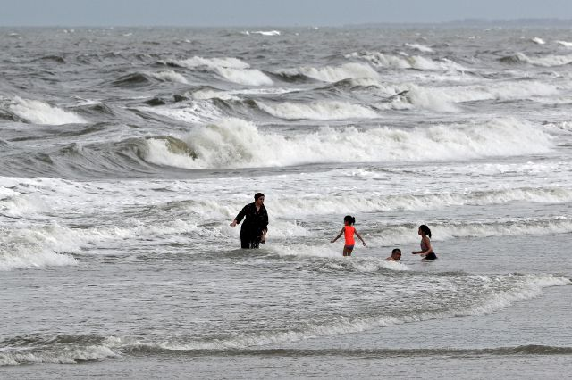 People swim in the ocean as Tropical Storm Isaias approaches in Kure Beach, N.C., Monday, Aug. 3, 2020. (AP Photo/Gerry Broome)