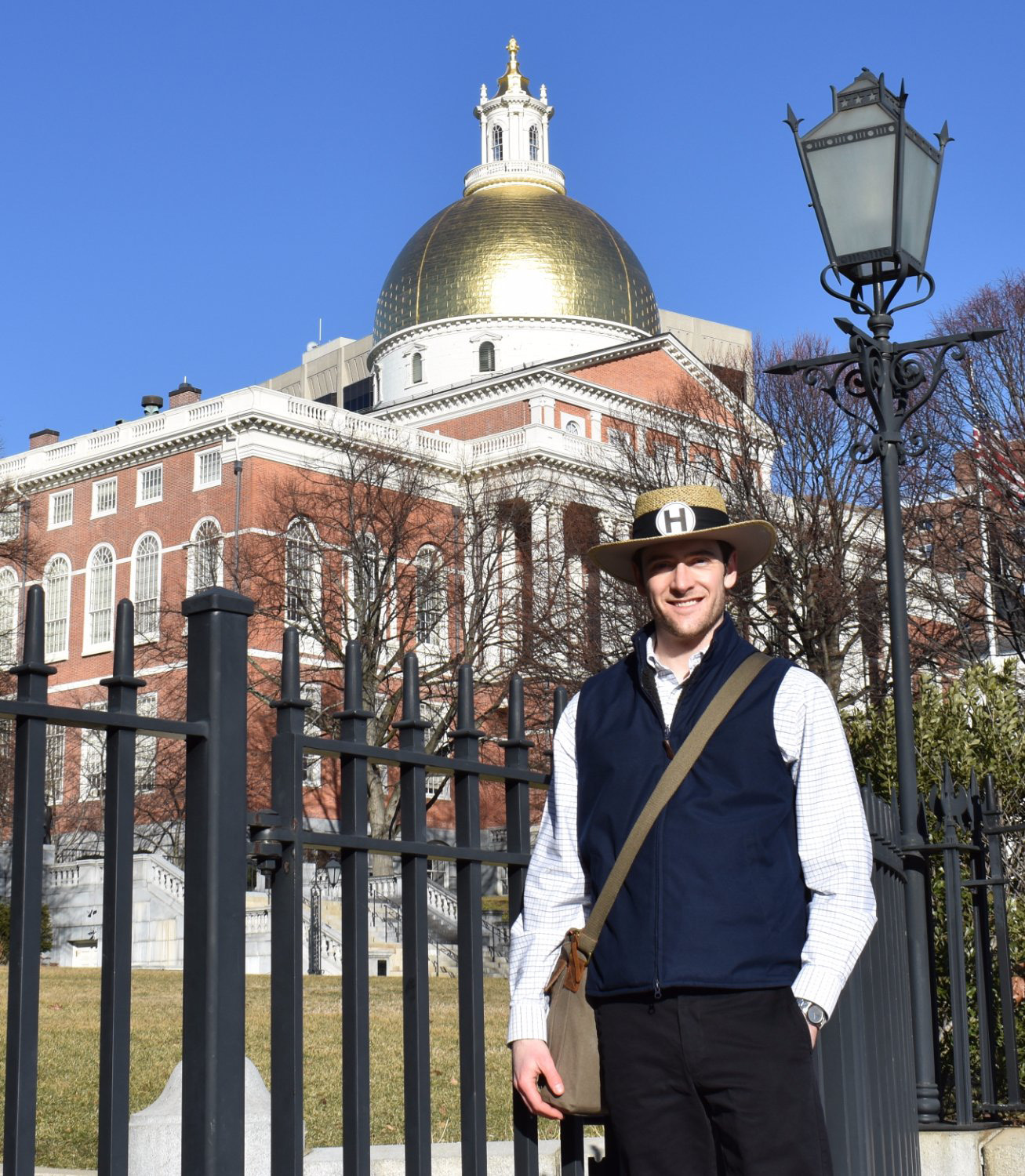Durham native and the man behind Hub Town Tours Ted Clark stands outside of the Massachusetts State House. The hat helps guests find the tour guide. | Submitted photo