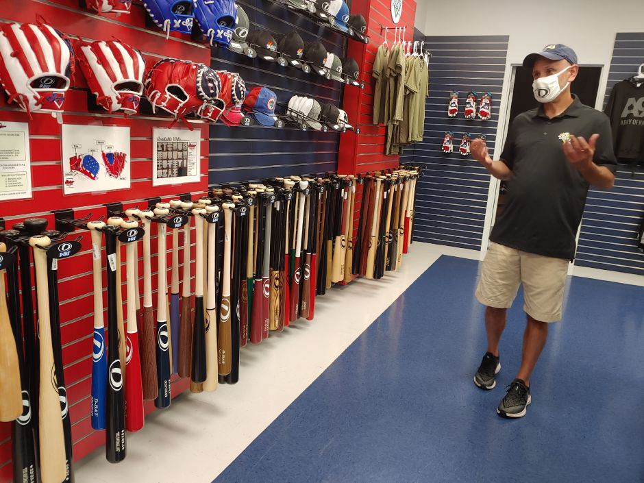 Owner Mark Szuchman explains what kind of equipment and clothing can be purchased in the D-Bat store. John Rook/Cheshire Herald