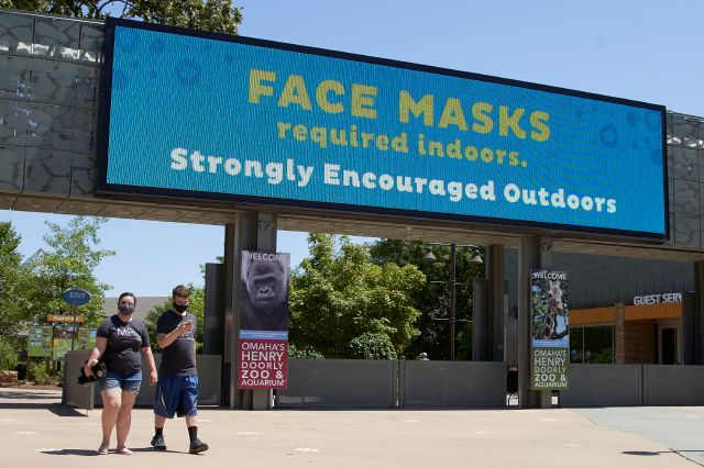 Visitors leave the Henry Doorly Zoo in Omaha, Neb., Monday, July 27, 2020, where face mask wearing is required indoors and encouraged in the outdoor areas. Nebraska