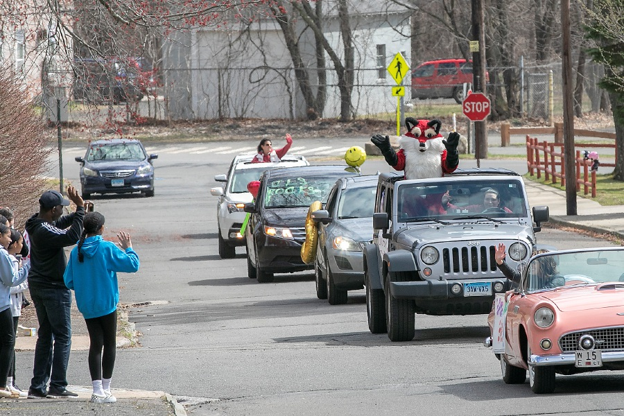 Southington students and their parents, left, wave to teachers and staff from Oshana Elementary School as they parade up Cowles Avenue in Southington on Tuesday. Principal Josephine Rogala and her husband Doug, right, wave from their pink Thunderbird convertible. See more photos online at myrecordjournal.com/News/Southington Photos by Dave Zajac, Record-Journal