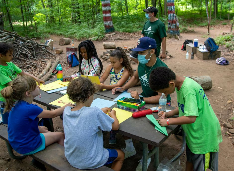 Camp counselor Brandon Hernandez draws with his campers as they sit in their campground area in the woods at the Meriden YMCA's Mountain Mist Day Camp on Friday, June 26, 2020. Each group has its own designated camping area where they do their arts and crafts, eat lunch, have campfires and spend time together. Aaron Flaum, Record-Journal