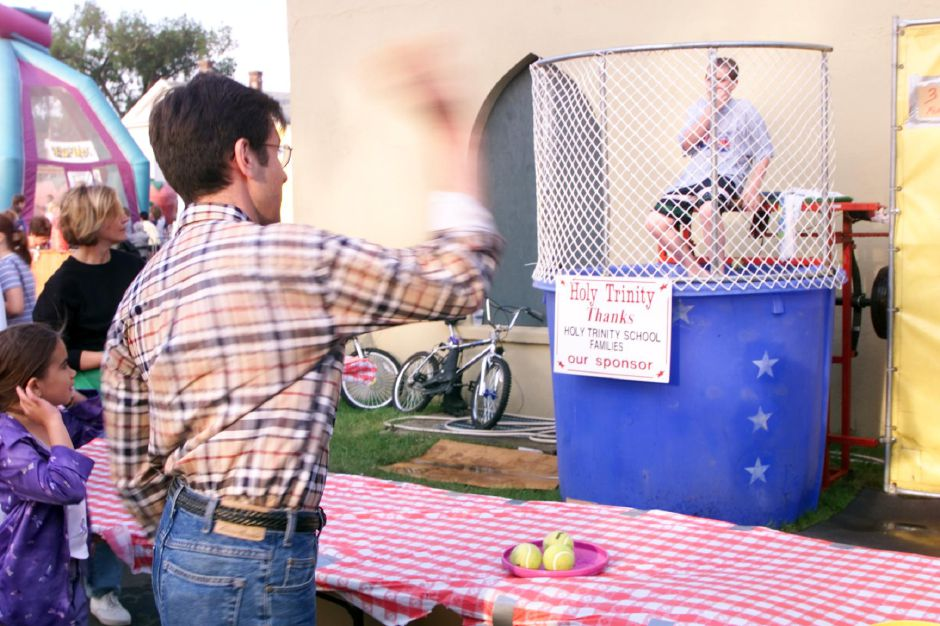 Mark Verselli, left, taks a shot at the dunking tank target as his son, Michael Verselli, 11, waits for the results Thurs., June 8, 2000 at the Holy Trinity Bazaar. He stayed dry on this attempt.