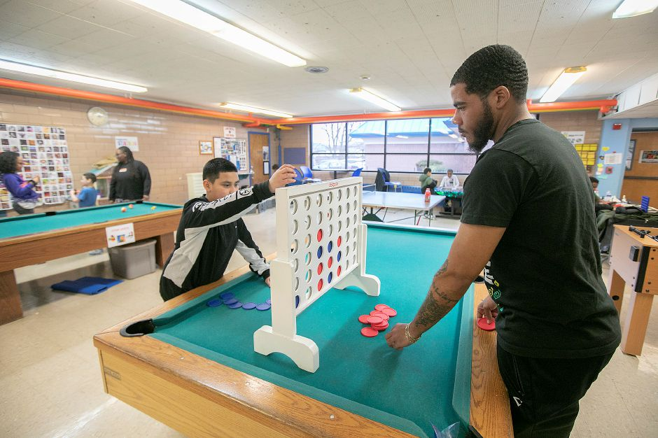 At left, Jovan Perez, 11, of Meriden, plays a game of Connect Four with Henry Rhodes lll, a behavior coordinator at the Boys and Girls Club.