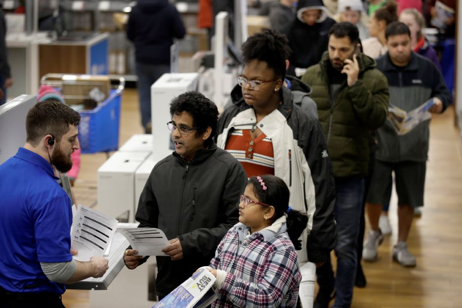 People wait in line to purchase a computer during a Black Friday sale at a Best Buy store Thursday, Nov. 28, 2019, in Overland Park, Kan. (AP Photo/Charlie Riedel)
