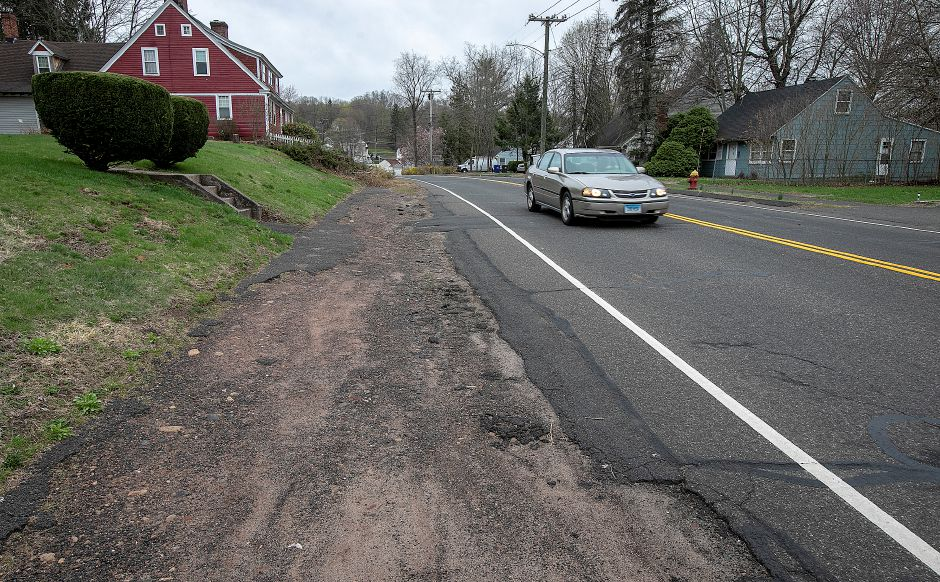 A motorist travels past a sidewalk in disrepair on Coe Avenue in Meriden, Thurs., Apr. 18, 2019. The city has received a $400,000 grant from the state Department of Transporation to extend the Hanover Pond Trail from behind Platt High School onto Coe Avenue. The trail will replace the existing sidewalk along Coe Avenue. Dave Zajac, Record-Journal