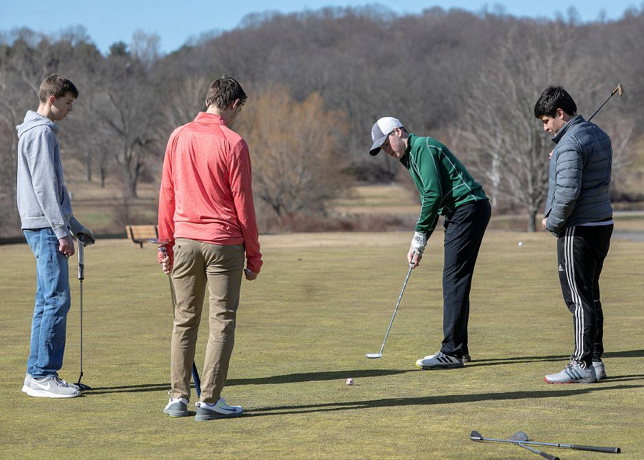 Left to right, Joshua Farnsworth, 16, Benjamin Pierce, 17, Matthew Bahre, 17, and Nick Camera, 18, all of Meriden, practice on the putting green at Hunter Golf Club in Meriden, Mon., Mar. 25, 2019. The course is getting an early jump on the 2020 season. It opens this Saturday and Saturday. Dave Zajac, Record-Journal
