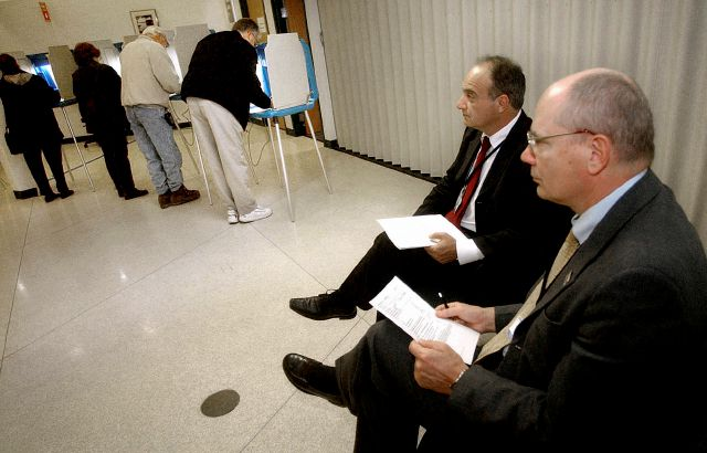 FILE - In this Nov. 2, 2004, file photo, parliamentarians Goran Lennmarker, right, of Sweden and Stavros Evagorow, of Cyprus, observe the American voting process as voters cast their ballots at Robbinsdale City Hall in Robbinsdale, Minn. The two men are members of the Organization for Security and Cooperation in Europe. Officials said Friday, Sept. 18, 2020, that due to the coronavirus pandemic, the security organization had drastically scaled back plans to send up to 500 observers to...