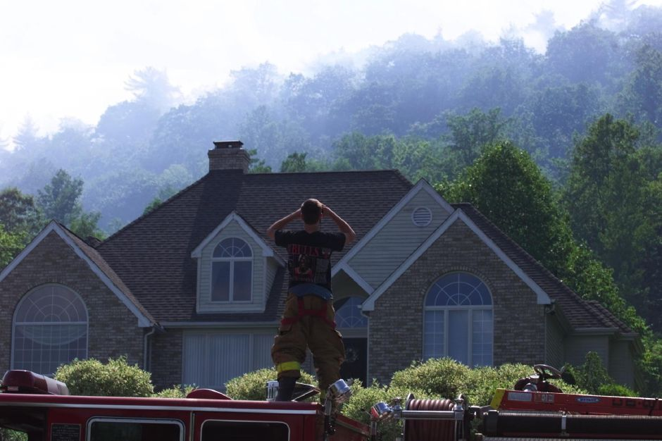 Perched atop a firetruck on Winding Ridge Road, Southington firefighter Chris Buechele uses binoculars to get a closer look at smoke-covered Southington Mountain. The fire or fires broke out June 3, 1999 afternoon with firefighters looking until the evening for access points to fight the blaze.