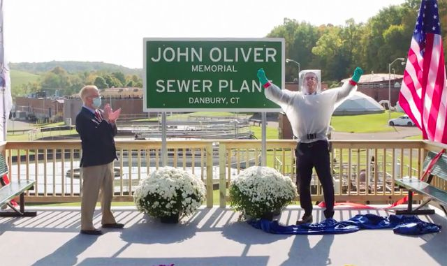 "This image taken from video released by HBO shows John Oliver, host of ""Last Week Tonight with John Oliver,"" right, with Mayor Mark Boughton during a dedication ceremony for The John Oliver Memorial Sewer Plant, in Danbury, Conn. Oliver made a secret trip to Connecticut last week to help cut the ribbon on a sign naming a sewage treatment plant in his honor. (HBO via AP)"