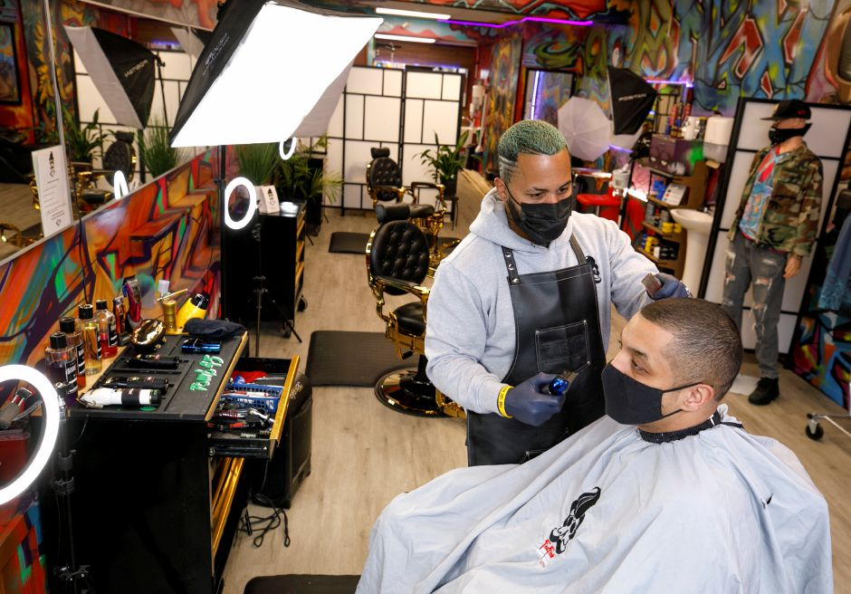Barber David Ortiz, owner of Feel Fresh Hair Studio, gives a trim to brother Armando Ortiz, of Meriden, at the 65 W. Main St. barbershop in Meriden on Thursday.