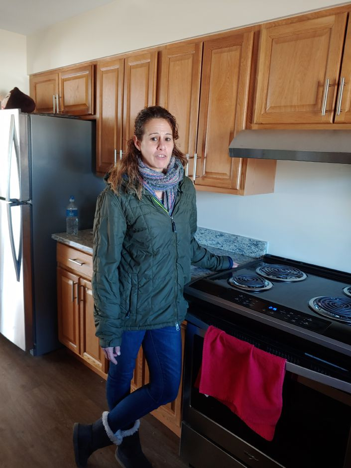 Yale Acres resident Nicole Murphy shows off her new kitchen after moving into a renovated unit with her two children last week. Mary Ellen Godin, Record-Journal