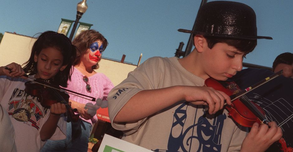 Katrina Riberio, left, and Ian Westermeyer, 12, both of Meriden, try playing violins at a music booth at the Arts at the Crossroads Festival on West Main Street in downtown Meriden Saturday afternoon September 18, 1999.